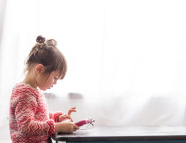 Girl-sitting-at-table-playing-with-digital-tablet