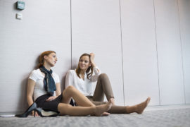 Tired-businesswomen-sitting-on-floor-in-office